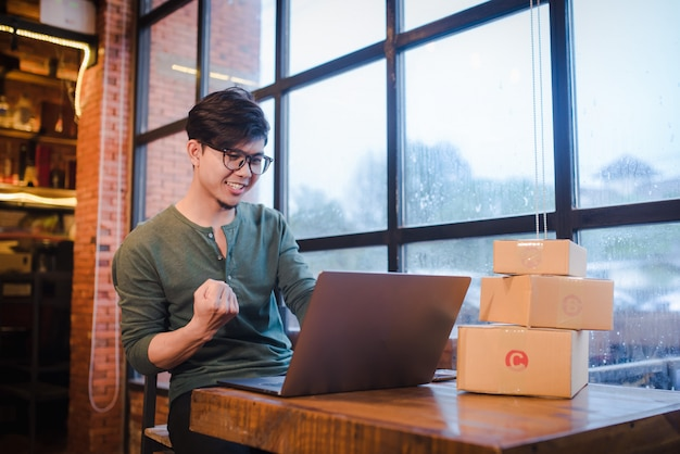 Young man sitting with computer and mobile phone on wooden floor with parcel selling ideas concept online. Premium Photo