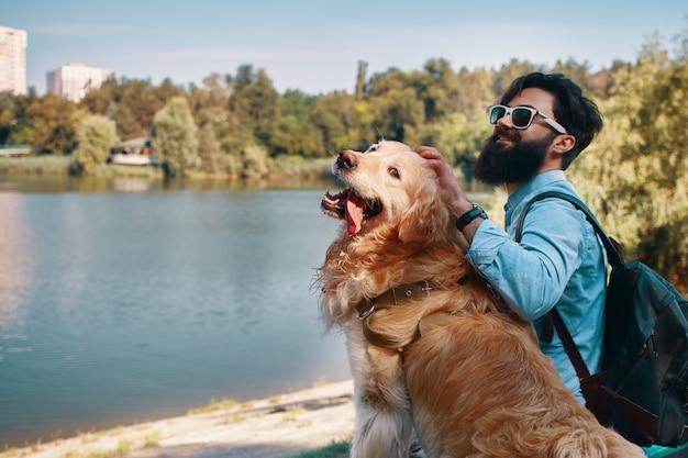 Молодой человек сидит со своей собакой на стуле в парке Бесплатные Фотографии