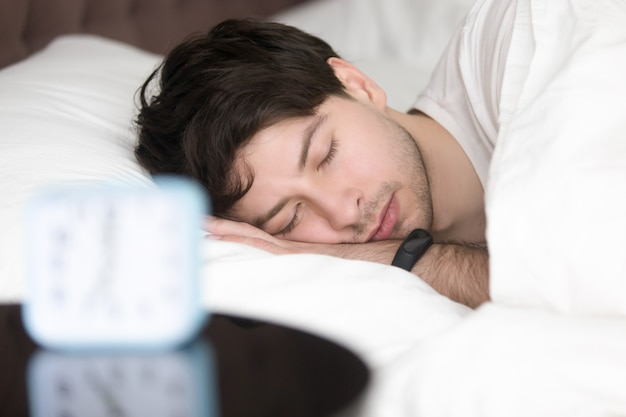 Young man sleeping next to alarm clock wearing smart wristband Free Photo
