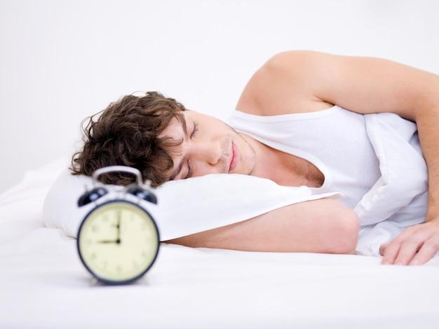Il giovane che dorme con la sveglia vicino alla sua testa Foto Gratuite