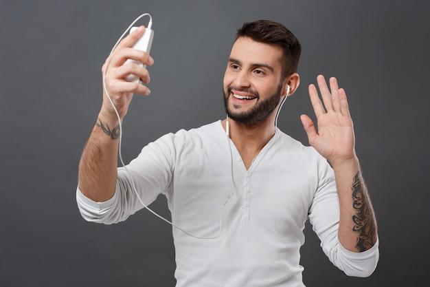灰色の壁を越えて電話挨拶を見て笑っている若い男 無料写真
