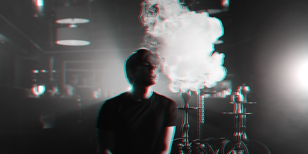 Young man smokes a hookah and lets out a cloud of smoke Premium Photo