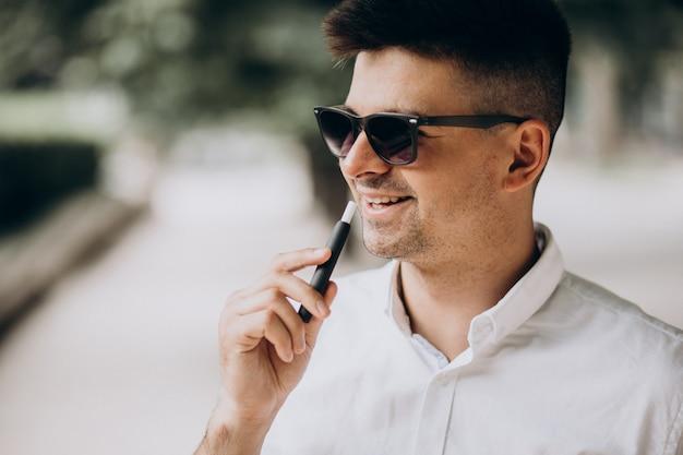 Молодой человек курит электро сигарету снаружи в парке Бесплатные Фотографии