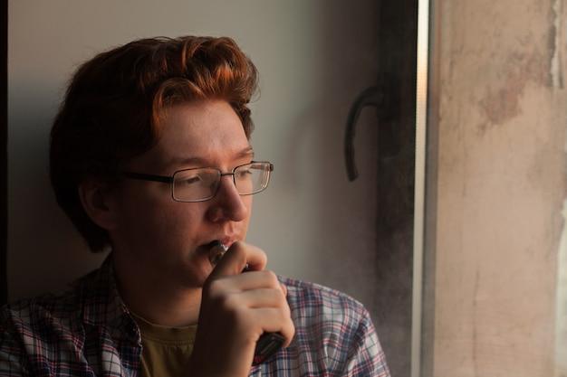 Young man smoking electronic cigarette. Premium Photo