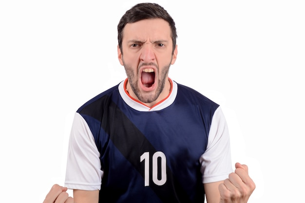 Young man in soccer football uniform screaming while his team win. Premium Photo