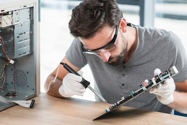 Young man soldering computer circuit over wooden desk Free Photo