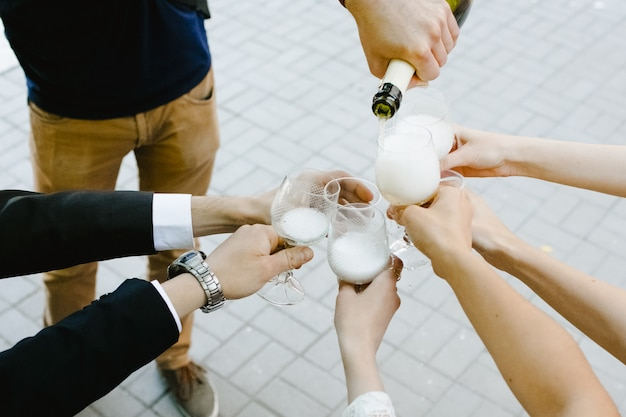 Young man spills champagne in his friends glasses Free Photo