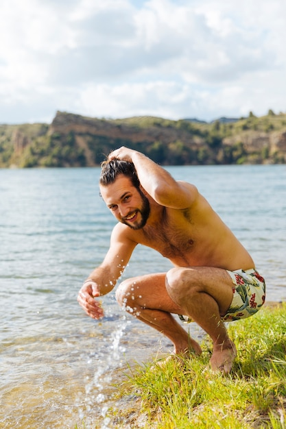 Young man splattering in water on river Free Photo