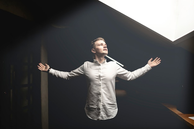 Young man spread his hands wide after getting achievment Premium Photo