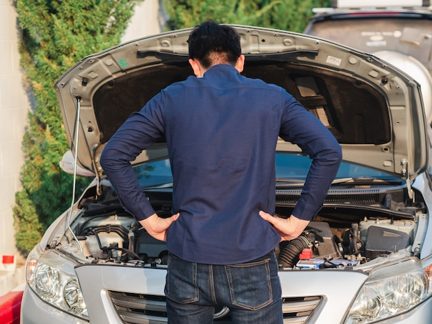 Young man standing in front of broken car for checking the car Premium Photo