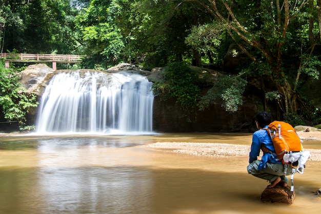Young man standing in front of waterfall with looking at waterfall and travel backpack in thailand Premium Photo