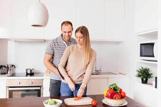 Young man standing behind his wife cutting the carrot with knife on chopping board Free Photo