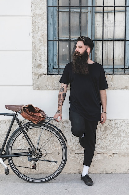 Young man standing near the bicycle looking away Free Photo