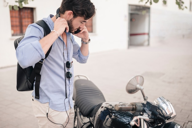 Young man standing near motorbike Free Photo