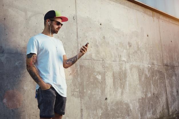 Молодой человек стоит рядом с серой бетонной стеной, смотрит на экран своего смартфона и слушает музыку в своих белых затычках для ушей Бесплатные Фотографии