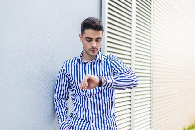 Молодой человек, стоя на улице, глядя наручные часы Premium Фотографии