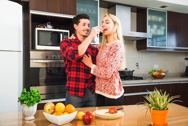 Young man standing behind the table feeding fruit slice to his wife Free Photo