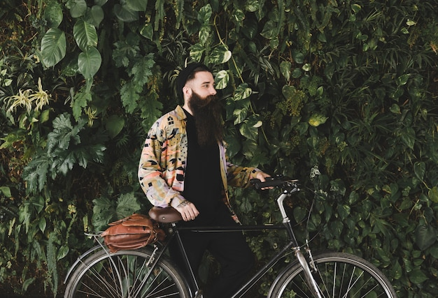 Young man standing with bicycle in front of green plants wall Free Photo