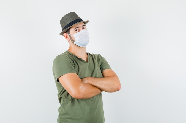 Young man standing with crossed arms in green t-shirt and hat, mask and looking confident Free Photo