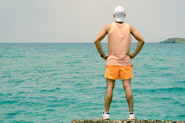 A young man stands on the edge of the pier, looks into the distance Premium Photo