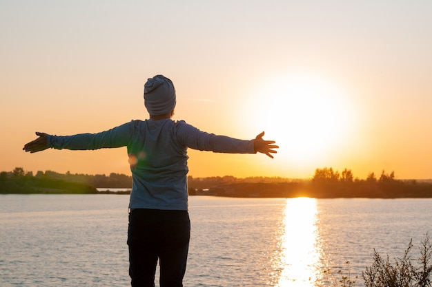 A young man stands on a lake at sunset Premium Photo