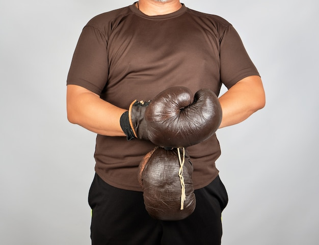 Young man stands and puts on his hands very old vintage brown boxing gloves Premium Photo