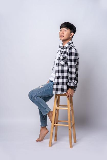 Un giovane con una camicia a righe è seduto su un seggiolone. Foto Gratuite