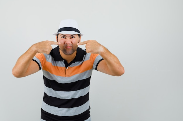 Young man in striped t-shirt,hat pointing at his nose and looking weird Free Photo