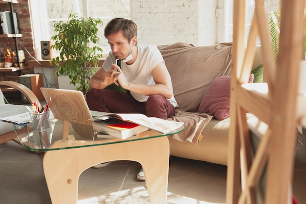 Young man studying at home during online courses Free Photo
