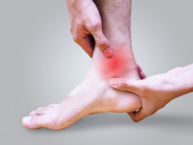 Young man suffering foot and ankle pain or sprained ankle. Premium Photo
