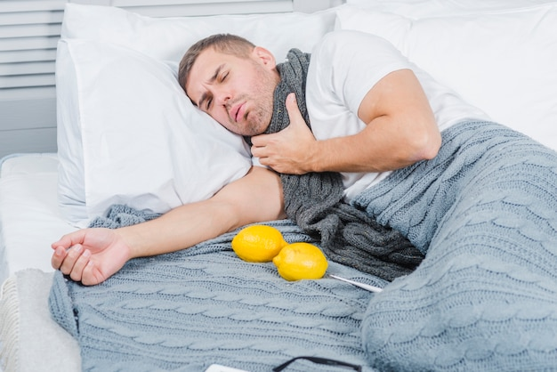 Young man suffering from sore throat lying on bed with lemon and thermometer Free Photo