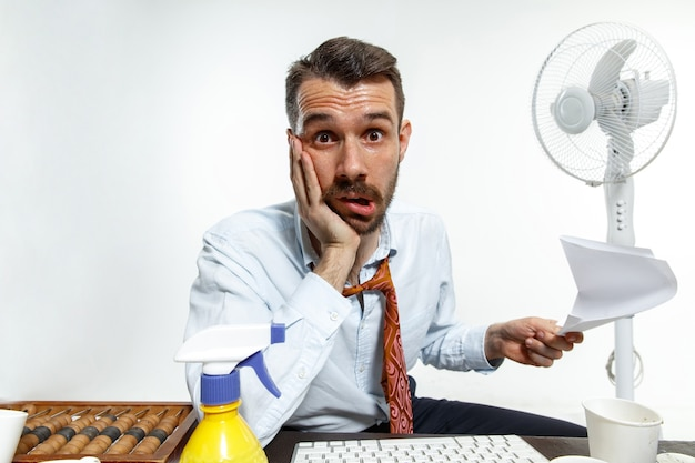 オフィスで暑さに苦しんでいる若い男 無料写真