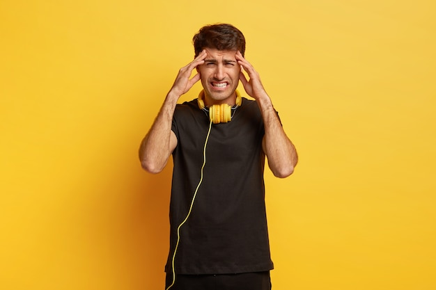 청년은 두통을 앓고, 사원에 손을 대고, 불쾌한 감정으로 치아를 움켜 쥐고, 검은 옷을 입고, 헤드폰을 사용합니다. 무료 사진