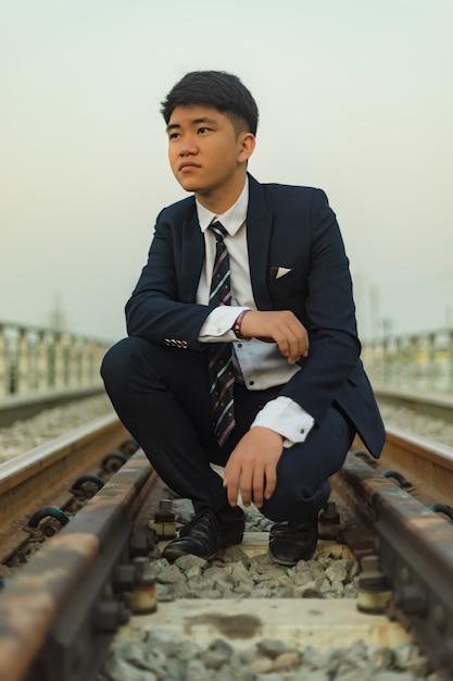 Giovane uomo in un vestito accovacciato nel mezzo di un ponte ferroviario che guarda lontano Foto Gratuite