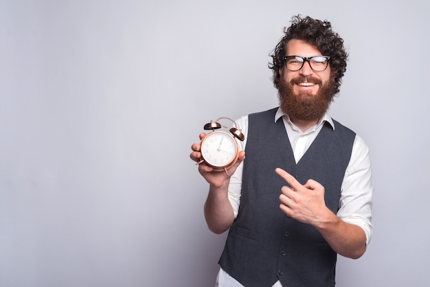 Young man in suit pointing at alarm clock on white. Premium Photo
