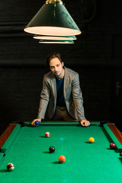 Young man in suit standing behind billiard pool holding ball in club Free Photo