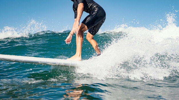 Young man surfs ocean clear water waves Free Photo