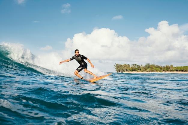 Молодой человек занимается серфингом на волнах океана с чистой водой Бесплатные Фотографии
