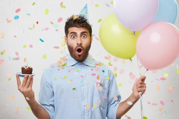 カップケーキと風船を持って紙吹雪に囲まれた若い男 無料写真