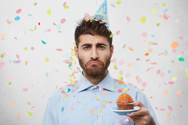 カップケーキを保持している紙吹雪に囲まれた若い男 無料写真