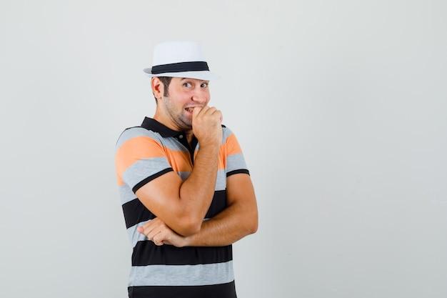 Giovane in maglietta, cappello che sorride segretamente e che sembra divertente Foto Gratuite
