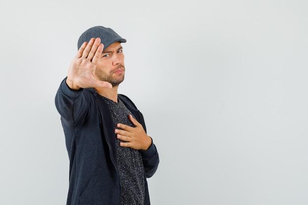 Giovane uomo in t-shirt, giacca, berretto che mostra il gesto di rifiuto, tenendo la mano sul petto, vista frontale. Foto Gratuite