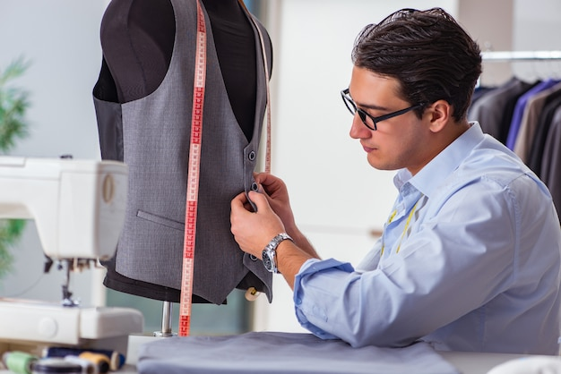 Young man tailor working on new clothing Premium Photo