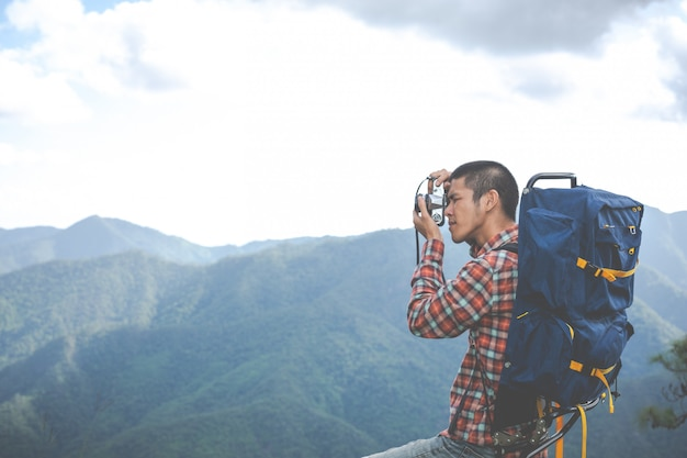 A young man takes pictures of mountain peaks in a tropical forest along with backpacks in the forest. adventure, travel, hiking. Free Photo
