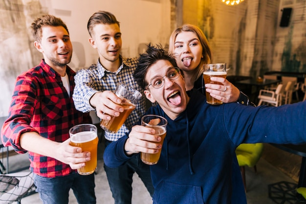 Young man taking selfie on mobile phone with his friends holding the glasses of beer Free Photo