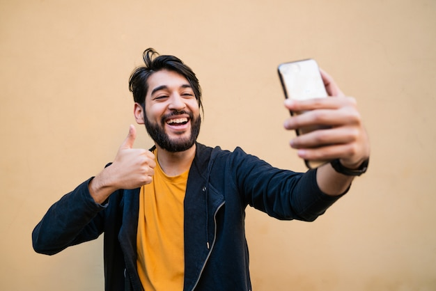 Young man taking selfies with phone. Free Photo