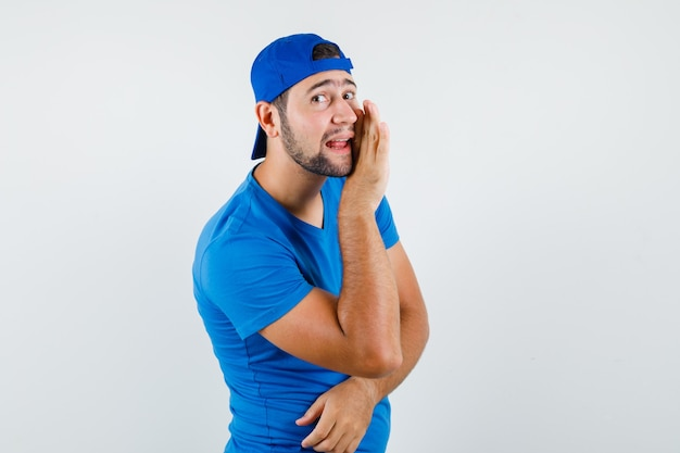 Young man telling secret behind hand in blue t-shirt and cap and looking gossipy Free Photo