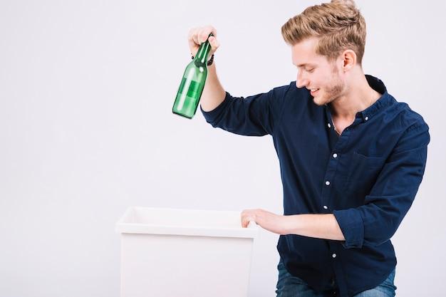 Młody Człowiek Wyrzucający Zieloną Butelkę Do Kosza Darmowe Zdjęcia