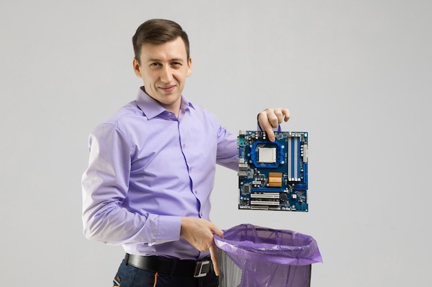 Young man throws motherboard in trash isolated on light background Premium Photo