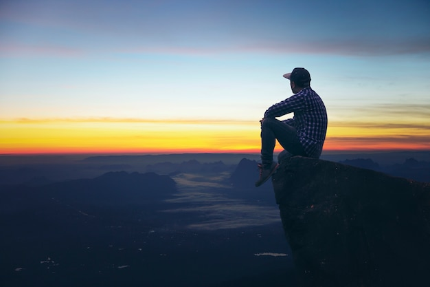 Young man tourists sit at the top of the rock beautiful view point sunrise with fog. Premium Photo